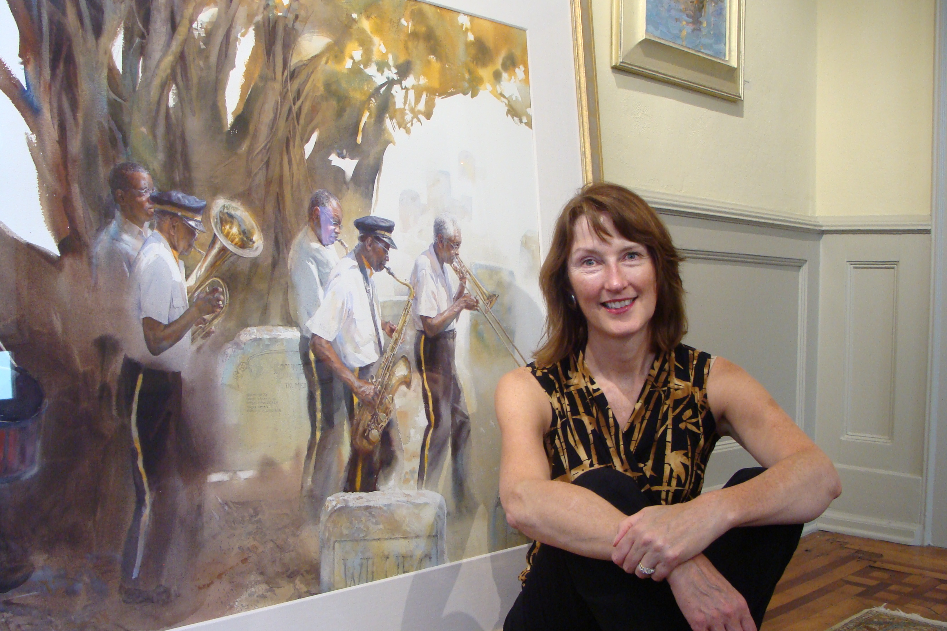 """Mary Whyte sitting in front of a recent painting from her """"Dying South"""" series."""