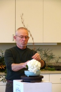 Dr. Earnest works on a Japanese flower arrangement.