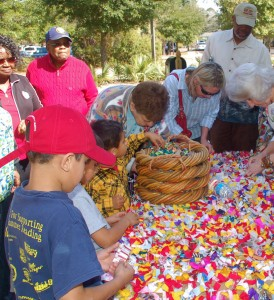 Attendees at the De Gullah Roots Festival add to Sharon Cooper-Murray's rag quilt.