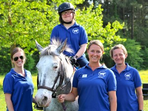 Michelle has progressed form riding with four helpers to being able to trot with just one assistant.