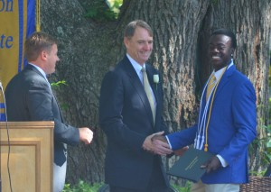 Bill McTigue, center, chairman of the Board of Trustees, and Hacker Burr, Charleston Collegiate School's Head, present Andre Coaxum with his diploma.