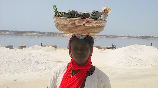 A Senagalese woman carries her wares in a sweetgrass basket.