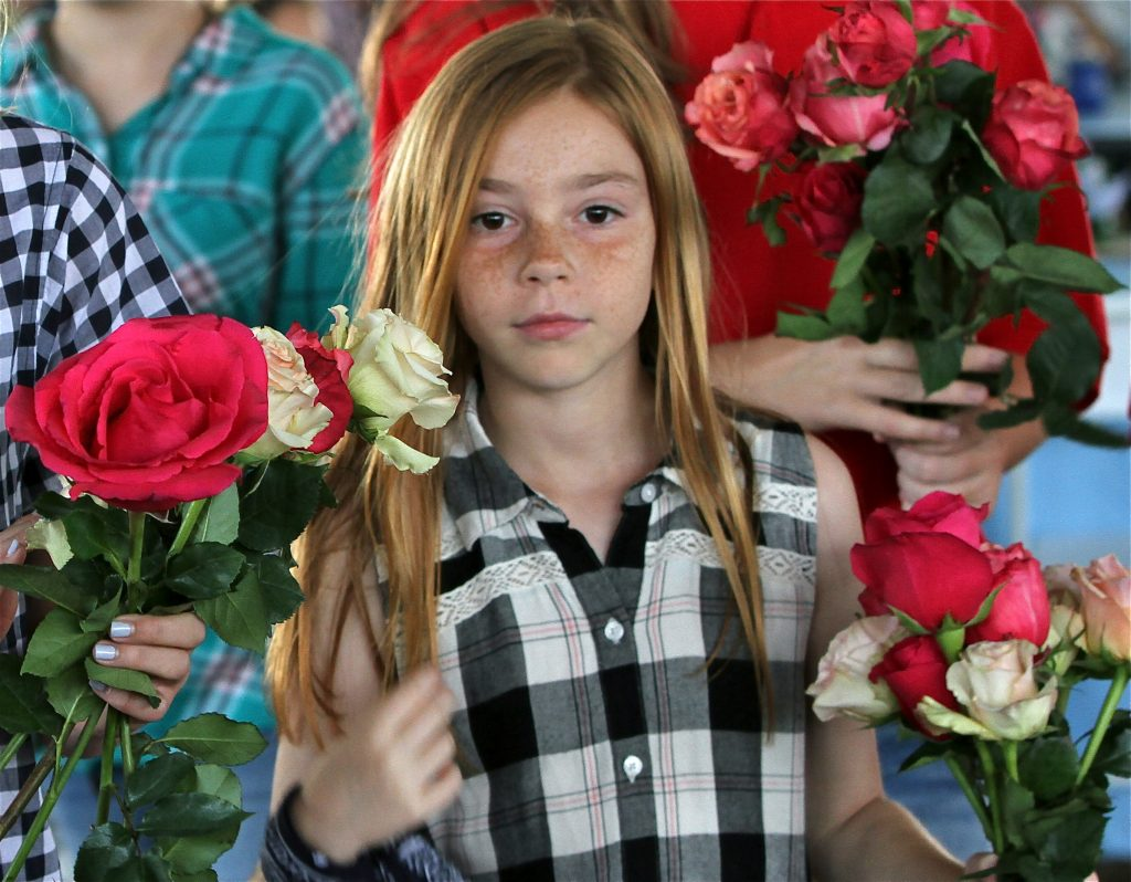 Ella Willits (BEC Pony Club Member), BEC Pony Club Members helped to give out roses to everyone who purchased a rose in our Run for the Roses auction. Each $100 donation supports a therapeutic riding lesson for one student.
