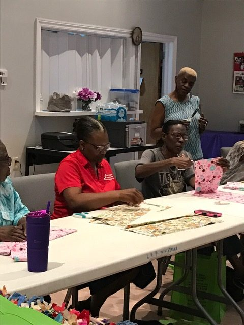 Sharron Cooper Murray demonstrating rag quilting technique to participants.